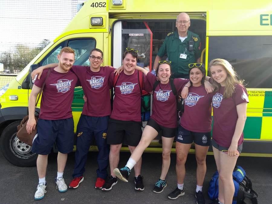 sports team posing outside ambulance
