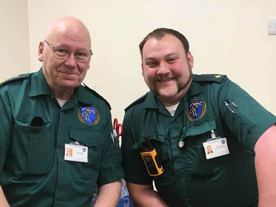 two paramedics smiling at the camera