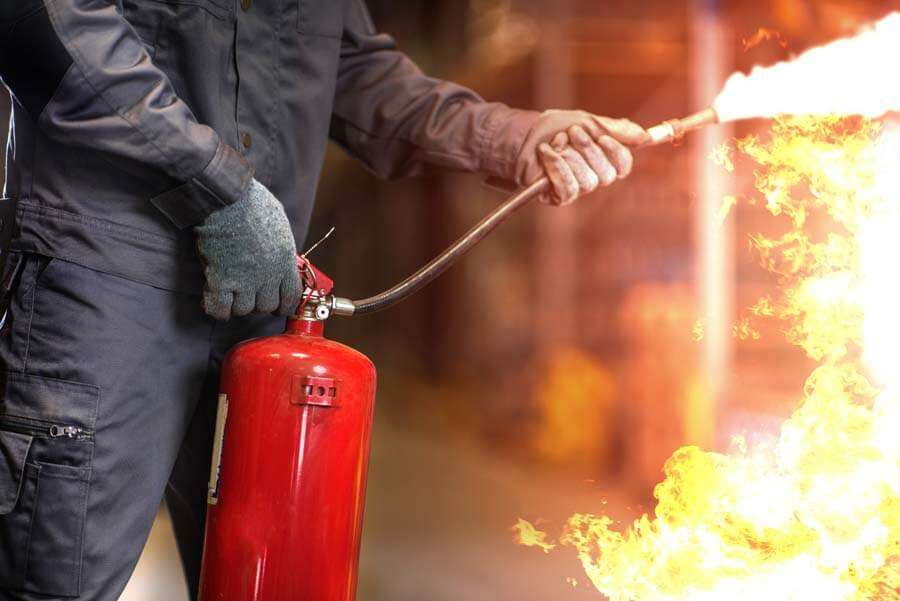 person using fire extinguisher on fire