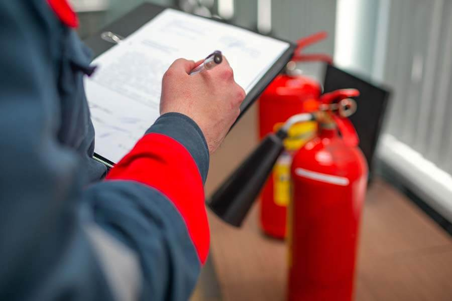 person inspecting fire extinguishers and making notes
